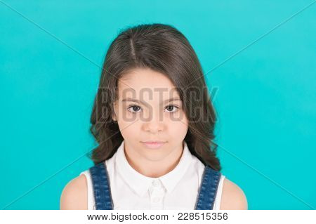Small Girl With Young Face Skin On Blue Background. Kid Model With Long Healthy Brunette Hair. Child