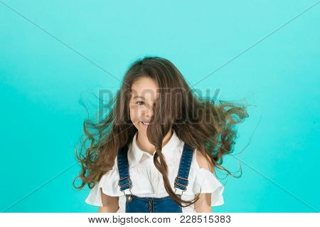 Girl Smile With Flowing Long Wavy Hair On Blue Background. Child Smiling With Healthy Brunette Hair.