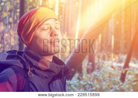 Young Man With Closed Eyes In Forest With A Sunbeam. Concept Of Relaxation