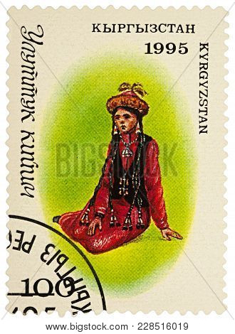 Moscow, Russia - February 25, 2018: A Stamp Printed In Kyrgyzstan, Shows Sitting Young Woman In A Tr