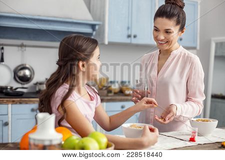 Vitamin Intake. Good-looking Glad Dark-haired Young Mother Smiling And Giving Vitamins To Her Daught