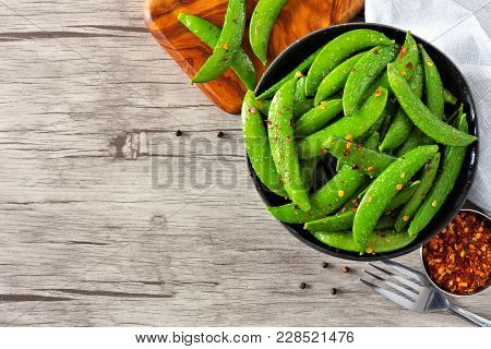 Bowl Of Healthy Roasted Snap Peas. Top View, Corner Orientation With Copy Space On A Wood Background