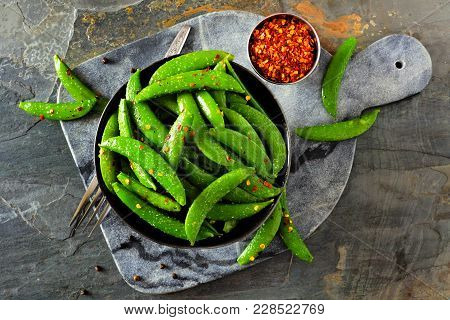 Bowl Of Healthy Roasted Snap Peas. Top View, Flat Lay On A Dark Paddle Board Over A Slate Background