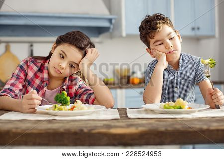 We Hate Vegetables. Attractive Sad Dark-haired Little Brother And Sister Sitting At The Table And Ha