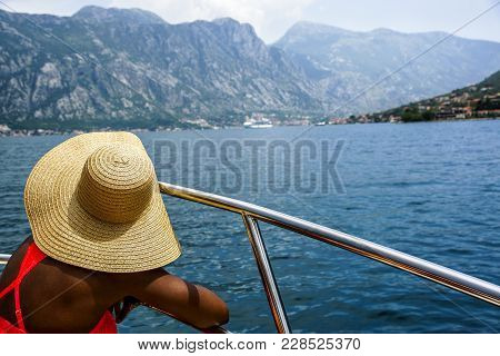 Woman In A Wide-brimmed Straw Hat Sits In The Boat And Looks At The Sea And Mountains. Back View. Mo