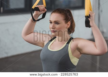 Curvy Girl Training On Suspension Straps In Gym