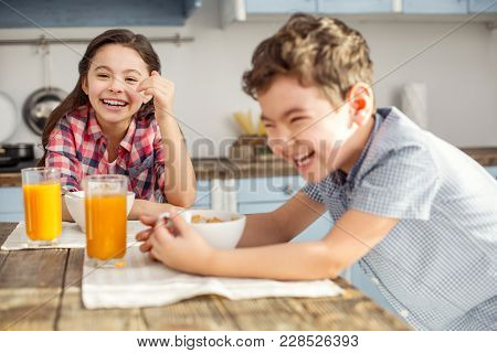 Having Fun Together. Pretty Joyful Little Dark-haired Girl Laughing And Having Breakfast With Her Br