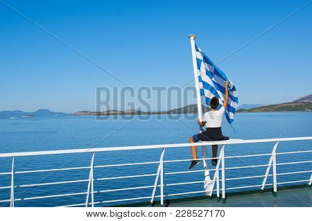 Boy Sitting On The Deck Of The Ship And Holding Greek Flag, Looking At The Blue Sea Landscape