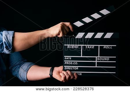 A Movie Production Clapper Board. Hands With A Movie Clapperboard On Black Background With Copy Spac