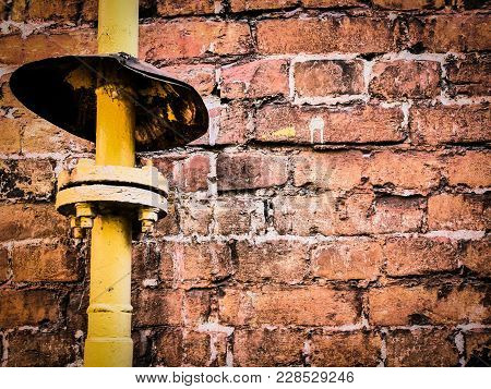 Small Visor Above Gas Tube Connection Near Old Brick Wall