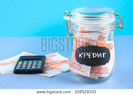 Bank with Russian money, 5000 rubles and a calculator on a gray background. Finance, moneybox, education. Text in Russian: credit poster
