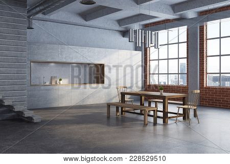 White Dining Room Interior With A Long Wooden Table, Two Chairs And A Gray Kitchen In The Background