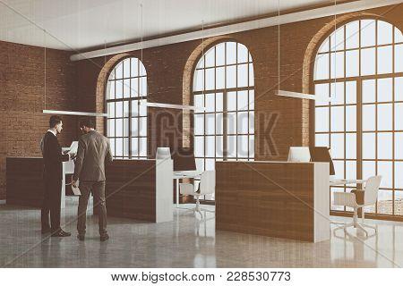Brick Open Space Office Corner With Arch Windows, A Concrete Floor And Cubicles. Businessmen. 3d Ren