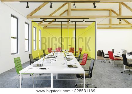 Yellow Wall Office Interior With White Tables, Computers, Green And Red Chairs. 3d Rendering Mock Up