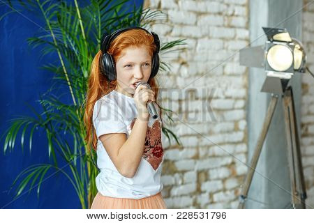 A Red-haired Child Sings A Song In A Microphone. The Concept Is Childhood, Lifestyle, Music, Singing