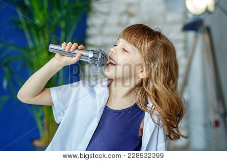 Little Beautiful Child Singing Into The Microphone. The Concept Is Childhood, Lifestyle, Music, Sing