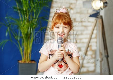 The Little Ore Girl Sings To The Microphone. The Concept Is Childhood, Lifestyle, Music, Singing, Li