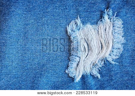 Fragment Of Jeans Trousers With Torn, Ripped Patch, Decorated With A Hole With Threads. Denim Backgr