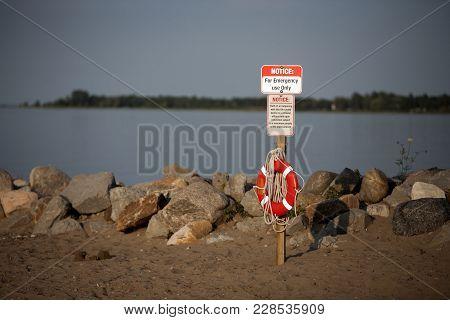 Orange And White Life Preserver Or Life Saver For A Beach Swim Near A Rocky Shore.
