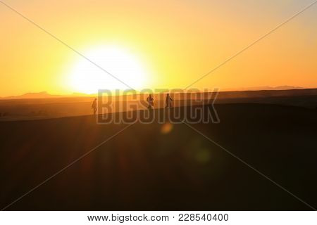 Silhouettes Of People Walking On The Edge Of A Dune In The Sahara Desert, With Golden  Sun And Glare