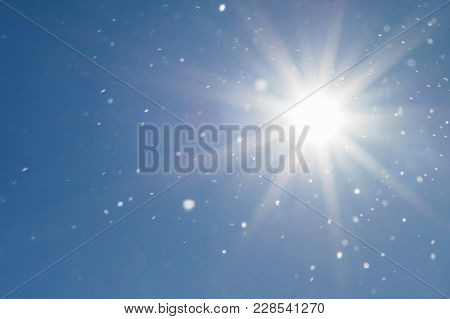 Background Of Cloudless Blue Sky And Sunbeams Illuminating Snow Flakes Into The Air