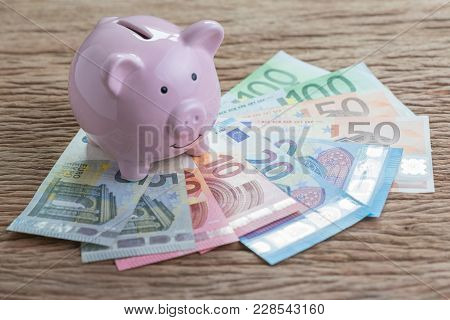 Pink Piggy Bank On Pile Of Euro Banknotes On Wooden Table, Financial Savings Money Account Or Europe