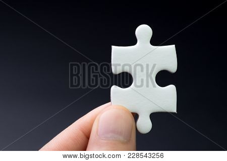 Business Strategy Missing Piece, Solution For Success Concept, Hand Holding A Bright White Paper Jig