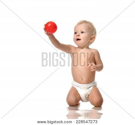 Infant Child Baby Toddler Sitting Naked In Diaper And Play With Red Ball Isolated On A White Backgro