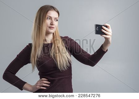 The Girl Makes Selfie On The Phone On A Gray Background, Isolate.