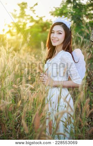 Angel Woman In A Grass Field With Sunlight