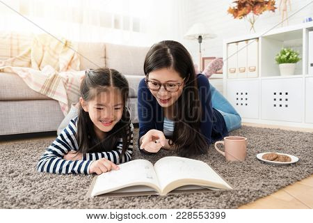 Asian Mother And Her Daughter Reading