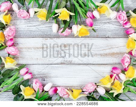 Assortment Of Spring Flowers Forming Heart Shape On White Rustic Wooden Boards