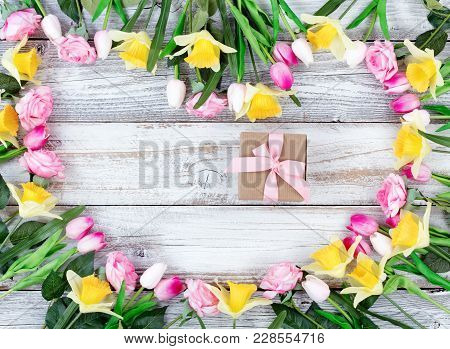 Assortment Of Spring Flowers Forming Heart Shape With Boxed Gift On White Rustic Wooden Boards