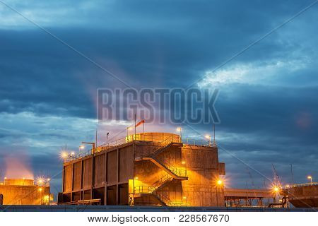 Aerial View Of Oil And Gas Industry, Refinery Factory, Petrochemical Plant At Sunrise With Cloudy Sk