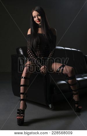 Sexy Brunette In Bdsm Style High-heels And Black Leather Dress Sitting On A Sofa In Dark Room