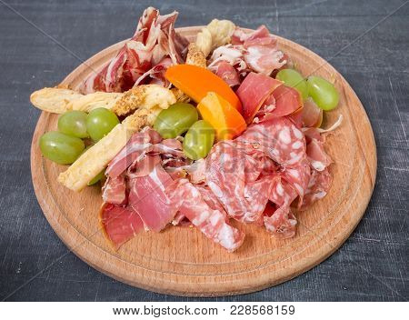 Mixed Italian Dried Meats Platter With Croutons And Grapes. Plate Located On A Black Table As A Back
