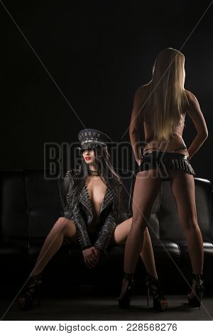 Two Slim Women Wearing Bdsm Style High-heels And Dresses Relaxing On A Black Sofa In Dark Room