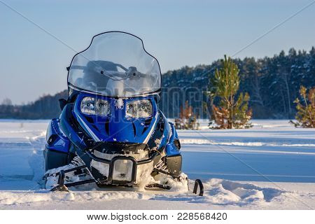 Snowmobile On A Snow Field Against The Forest. Recreation Concept On Nature In Winter Holidays. Wint