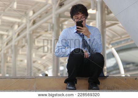 Unemployed Young Asian Man Looking For Job In Mobile Smart Phone. Unemployment People Concept.