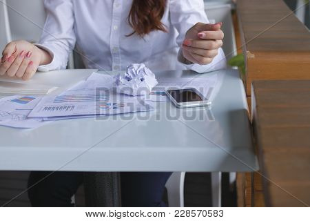 Selective Focus On Crumpled Paper On The Desk With Paperwork Or Charts And Frustrated Employee Feeli