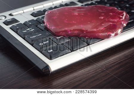 The Red Slime Spread On The Computer Keyboard. Tools For Quick Cleaning Of Dust In Hard To Reach Pla