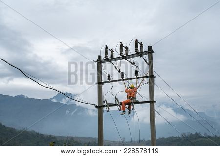 Electricians Working High On Electricity Pole In Vietnam
