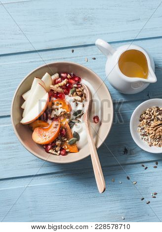Persimmon, Apple, Walnuts, Pomegranates, Seeds And Natural Yogurt. Healthy Food Concept On Blue Back