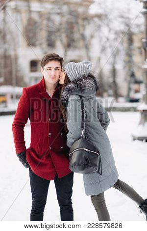 Young Couple In Love Outdoor Winter. Grlfriend Kisses A Guy