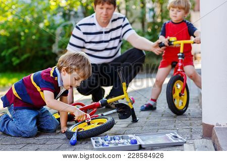 Two Happy Little Kid Boys And Father Repair Chain On Bikes And Change Wheel Of Balance Bicycle. Fami