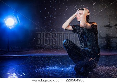 Attractive Young Man In Black Wet Clothes Under The Rain And Splash Of Water During Studio Photo Sho