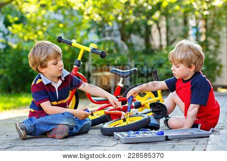Two Happy Little Kid Boys Repair Chain On Bikes And Change Wheel Of Balance Bicycle. Siblings Work T