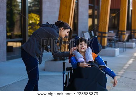 Eleven Year Old Disabled Boy In Wheelchair Listening To Music With Earbuds With The Help Of Caregive