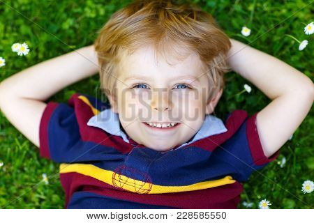 Happy Little Blond Child With Blue Eyes Laying On The Grass With Daisies Flowers In The Park. On War