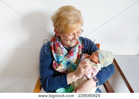 Happy Grandmother Holding Newborn Baby Grandchild On Arms In Hospital. Proud Senior Woman With Cute